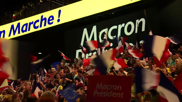 Interior shots of Emmanuel Macron supporters at a rally waving Tricolour flags and banners cheering on 17 April 2017 in Paris France