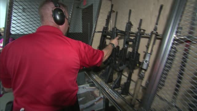 interior shots of firing range employee checking automatic machine gun performing safety check and then putting it away in metal wired cage man... - man and machine stock videos & royalty-free footage