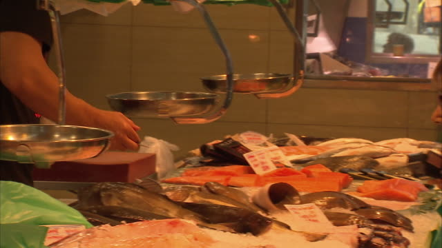 vídeos de stock e filmes b-roll de interior shots of fish stall at santa caterina indoor market people shopping at stall and staff weighing and preparing fish in barcelona on 6th... - balança instrumento de pesagem