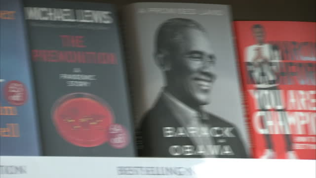 interior shots of footballer, marcus rashford's new book 'you are a champion' next to barack obamas book 'a promised land' on a shelving display in a... - book stock videos & royalty-free footage
