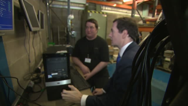interior shots of george osborne mp chancellor walking into a warehouse full of reconditioned computers and meeting a job seeker who is being trained... - チャンセラー点の映像素材/bロール
