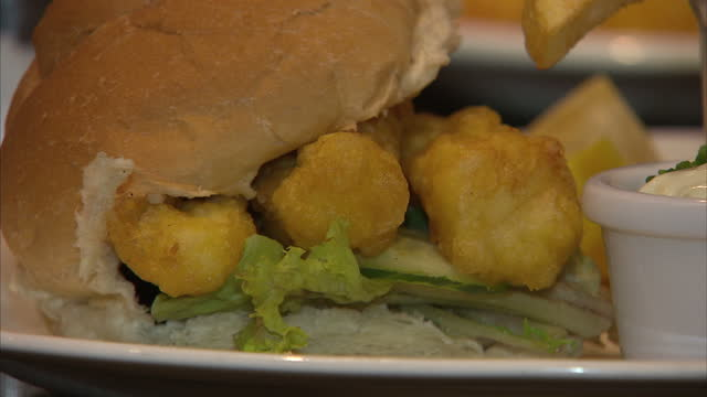 interior shots of gourmet fish finger sandwiches and chips on plates in a restaurant on september 24 2015 in london england - breaded stock videos and b-roll footage