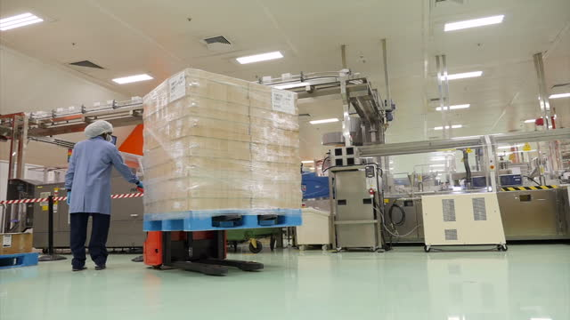 vídeos de stock, filmes e b-roll de interior shots of gsk employees on the factory floor of a toothpaste production line moving pallets of toothpaste around on february 03 2017 in... - moving activity