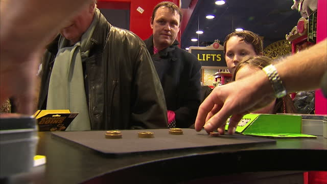 interior shots of hamley's employee demonstrating magic trick from marvin's magic with coins at counter in shop with children and parents looking on... - magic trick stock videos and b-roll footage