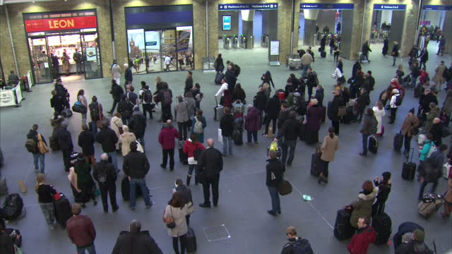 Interior shots of high winds shaking a crane near Kings Cross Station and crowds of travellers on the station concourse with departure boards...