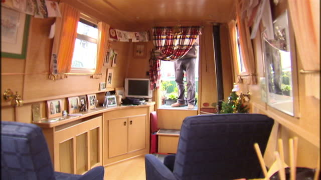 vídeos de stock e filmes b-roll de interior shots of houseboat resident walking into the living quarters of his comfortable modern houseboat living on boats has risen by 50 per cent on... - barco casa