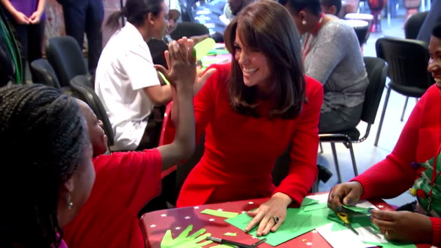 vidéos et rushes de interior shots of hrh catherine duchess of cambridge sitting at table talking to children about football she says william supports aston villa she... - robe rouge