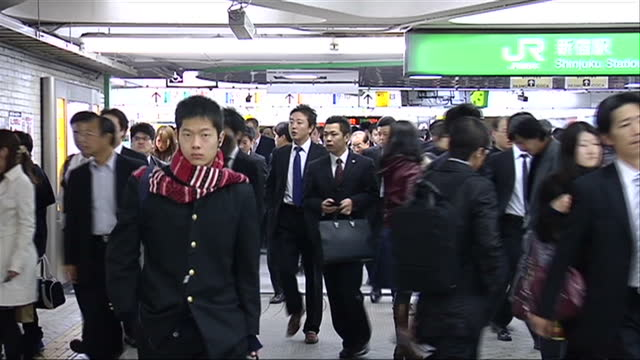 Interior shots of Japanese commuters on JR trains subway system including a salary man reading the newspaper and train announcements in Japanese and...