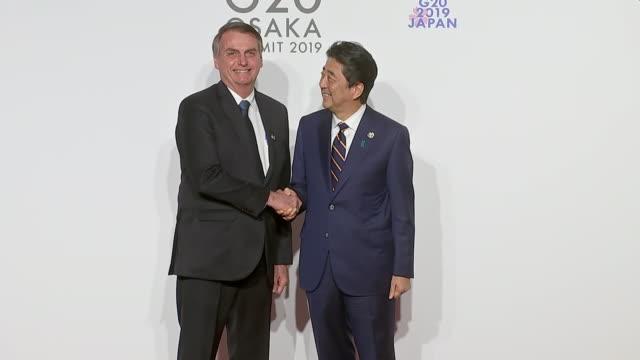 stockvideo's en b-roll-footage met interior shots of japanese prime minister shinzo abe shaking hands with brazillian president jair bolsonaro at the g20 summit on 28 june 2019 in... - minister president