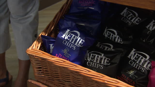 interior shots of kettle chips crisps on sale and a woman buying a packet and a chocolate brownie on august 26, 2015 in london, england. - snack stock videos & royalty-free footage