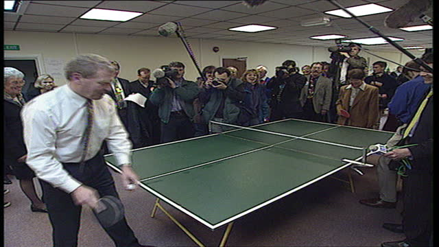 Interior shots of Leader of the Liberal Democrats Paddy Ashdown meeting a woman at a calligraphy class and playing table tennis at a community centre...