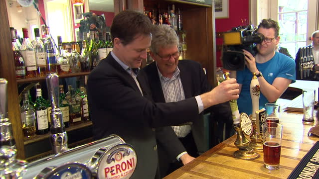 interior shots of liberal democrats leader nick clegg pouring a pint of ale for local supporters inside the queen's head pub on april 06 2015 in bath... - ニック クレッグ点の映像素材/bロール