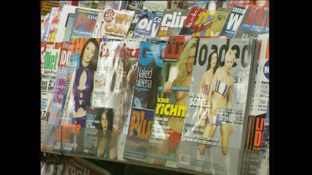interior shots of loaded magazine fhm and esquire magazine on shelves in a newsagent - for him magazine点の映像素材/bロール