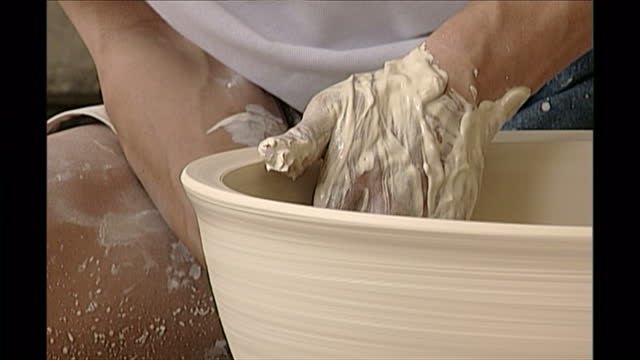 interior shots of man making clay pot on a pottery wheel in a factory on may 08, 1998 in jingdezhen, jiangxi province, china. - porcelain stock videos & royalty-free footage