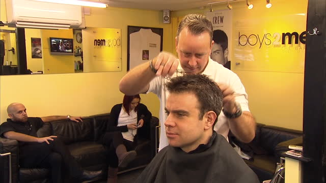 interior shots of man sitting in barbers chair having hair cut trim from hair dresser using scissors and comb man getting haircut in barbers chair on... - barber chair stock videos & royalty-free footage