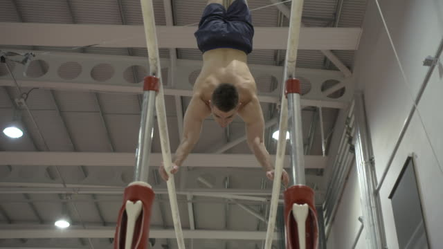 stockvideo's en b-roll-footage met interior shots of max whitlock at training on the parallel bars shot in the summer of 2019 - de brug