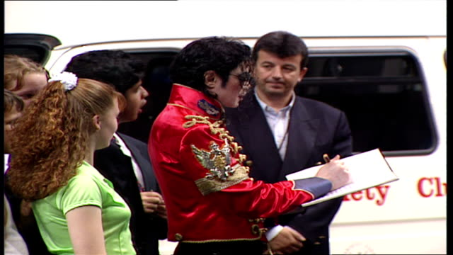 vidéos et rushes de interior shots of michael jackson signing autographs for disabled children and speaking to them before leaving event - autographe