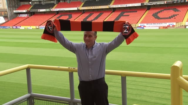 interior shots of micky mellon's unveiling as dundee manager. showing him holding a scarf and sitting in the stands at kilmac stadium at dens park. - torschuss stock-videos und b-roll-filmmaterial