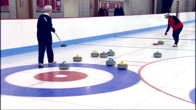 interior shots of middle aged women curling on ice low shot of stones rocks from pov behind sweeping brooms middle aged women sitting having lunch... - スコットランド スターリング点の映像素材/bロール