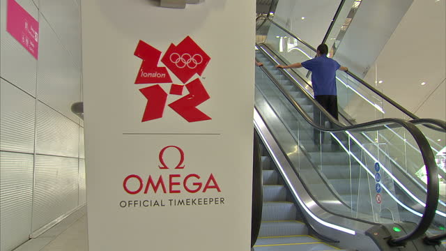 interior shots of olympic branded omega sign at escalator at the olympic site in stratford sky news 2012 olympics coverage at olympic village... - ロンドン ストラトフォード点の映像素材/bロール