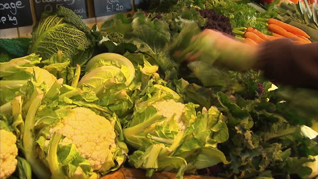 interior shots of organic fresh fruit and vegetables on the shelves of a farm shop as a greengrocer puts out more stock including parsnips carrots... - cauliflower stock videos & royalty-free footage