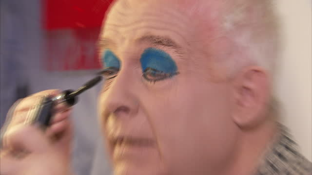 vídeos y material grabado en eventos de stock de interior shots of pantomime actor christopher biggins putting on his mascara eye makeup in the dressing room while getting ready to perform as widow... - maquillaje para ojos