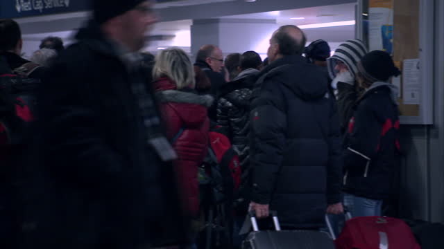 interior shots of passengers in penn station terminal walking with luggage in winter coats as a recorded announcement reads out train departure times... - new york city penn station stock videos & royalty-free footage