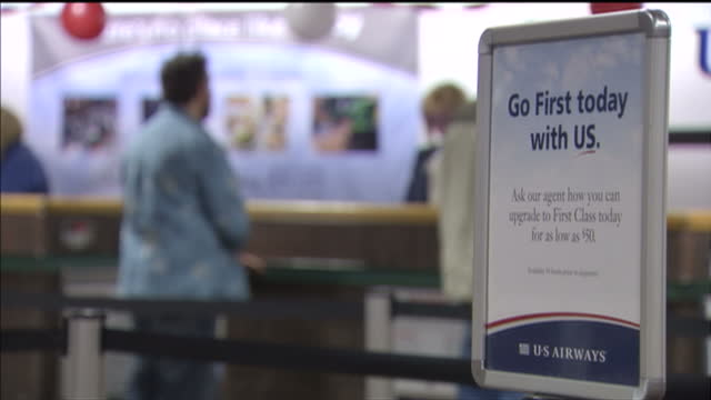 stockvideo's en b-roll-footage met interior shots of passengers in phoenix sky harbor international airport checking in their suitcases at a us airways check in desk and using self... - us airways