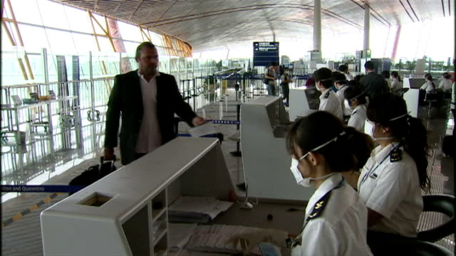 stockvideo's en b-roll-footage met interior shots of passengers passing through beijing airport passport control having their passports and visas stamped by chinese customs officers... - varkensgriep