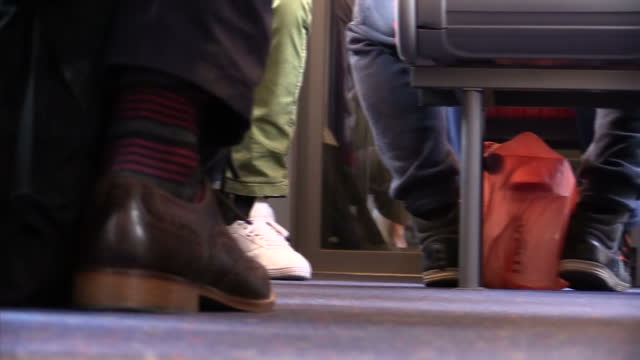 interior shots of passengers seated on a train including a shot of people's feet on the floor of the train>> on august 20 2014 in london england - bahnreisender stock-videos und b-roll-filmmaterial