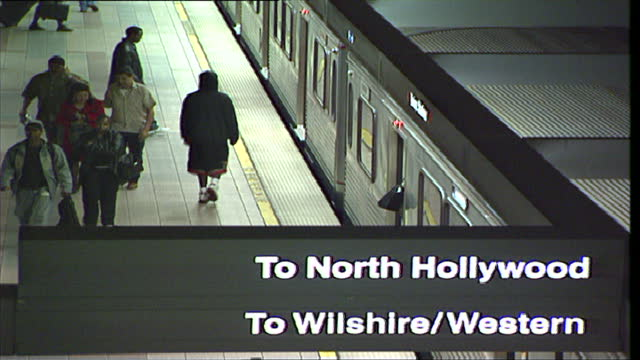 interior shots of passengers waiting on a station platform for a metro train bound for north hollywood and wilshire blvd then metro train approaches... - bahnreisender stock-videos und b-roll-filmmaterial