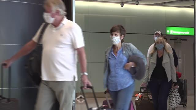 interior shots of passengers walking through heathrow terminal 2 international arrivals area, many wearing face masks, before the uk's two-week... - flughafen heathrow stock-videos und b-roll-filmmaterial