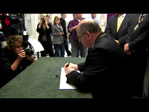 vídeos de stock, filmes e b-roll de interior shots of pat convery, lord mayor of belfast, signing book of condolence in memory of alex higgins who died of cancer on saturday. interior... - 50 segundos ou mais