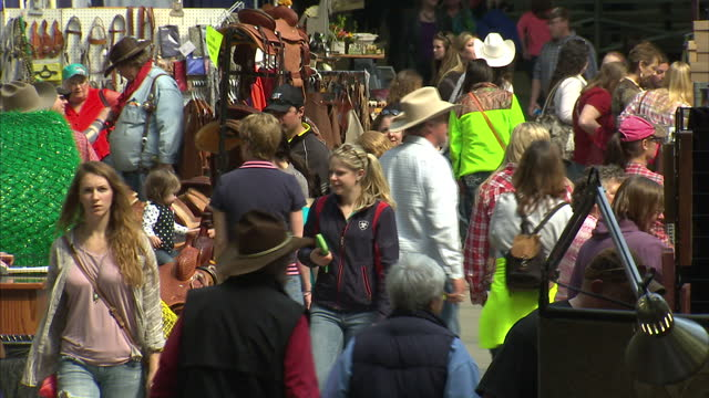 Interior shots of people at Iowa State Fairground browsing various stalls selling Western goods such as cowboy hats leather saddles and the like on...