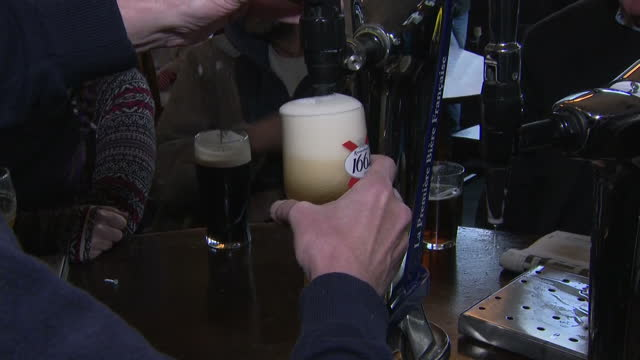 interior shots of people drinking pints of beer and other alcoholic drinks in a pub, and a barman pouring a pint of kronembourg lager on 4 november... - lager stock videos & royalty-free footage