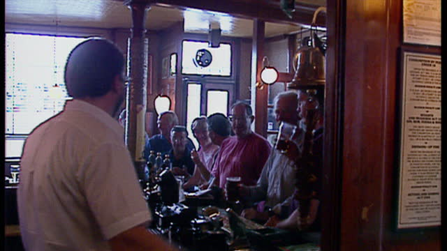 interior shots of people drinking pints of lager in a pub and the bar tender calling last order by ringing a bell behind the bar, customers all boo.... - cultures stock videos & royalty-free footage