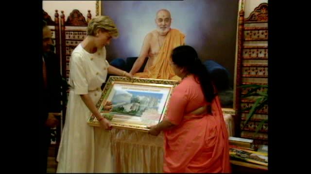 Interior shots of people giving gifts to Princess Diana on her visit to Shri Swaminarayan Mandir Hindu Temple and an interview with one of the gift...