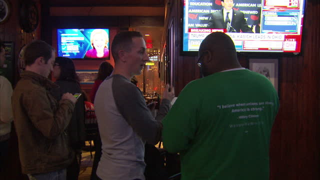 vídeos de stock, filmes e b-roll de interior shots of people in a bar drinking and watching tv coverage of the ohio state primaries on march 16 2016 in cleveland ohio - primary election