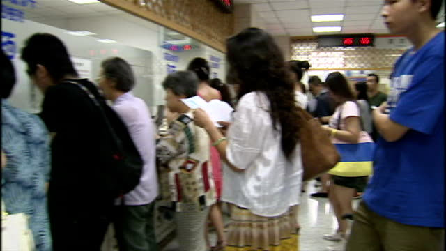 interior shots of people in a traditional chinese herbalist clinic queueing up to be served at the counter and be served by a white coated herbalist... - chinese herbal medicine stock videos and b-roll footage