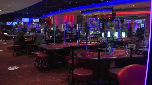 interior shots of people playing slot machines in a grosvenor casino, a dealer dealing at a craps table and a roulette wheel with people wearing face... - craps stock videos & royalty-free footage