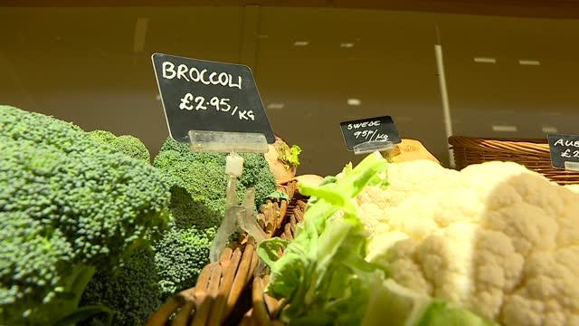 vídeos y material grabado en eventos de stock de interior shots of people shopping in a farm shop with various vegetables on display including carrots broccoli leeks and onions on 8 march 2017 in... - vegetal con hoja