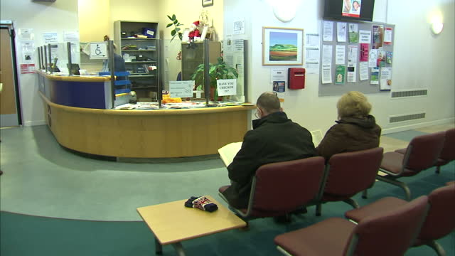 Interior shots of people sitting in a GP's waiting room close up shots of reception sign on December 29 2016 in Middlesbrough England
