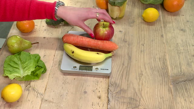 Interior shots of pieces of fruit and vegetables being placed on a scale to illustrate the recommended 800g or 10 portions that experts say people...