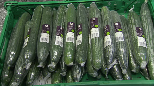 stockvideo's en b-roll-footage met interior shots of plastic wrapped cucumbers on display amongst other fruits and vegetables in a coop supermarket on november 08 2017 in london england - dranken en maaltijden
