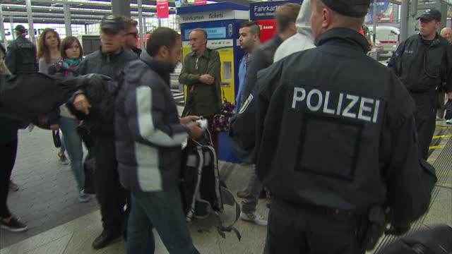 interior shots of police on station platform meeting refugees as they arrive in munich, germany, checking bags and documents, and gathering them... - 2015 stock-videos und b-roll-filmmaterial