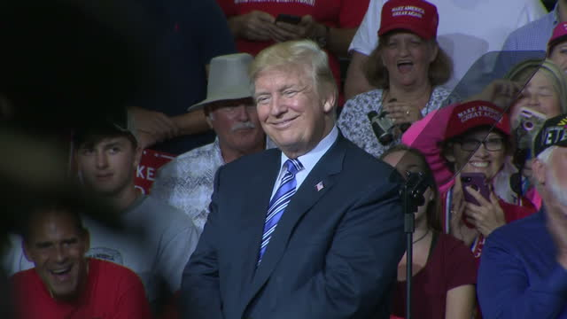 vídeos de stock e filmes b-roll de interior shots of president donald trump smiling on stage during a rally and addressing crowds of cheering supporters - comício político