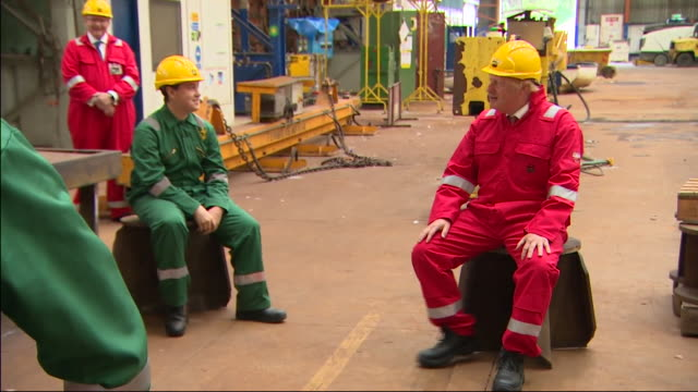 interior shots of prime minister boris johnson talking to workers on a visit to a shipbuilding yard wearing hard hat and overalls on 25 august 2020... - manual worker stock videos & royalty-free footage
