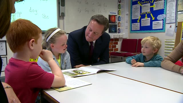 Interior shots of Prime Minister David Cameron encouraging a young girl to read a story during a visit to a primary school in Bolton the small girl...