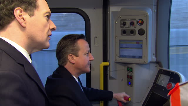 interior shots of prime minister david cameron next to chancellor george osborne driving a new london tube train along a piece of test track, during... - premierminister stock-videos und b-roll-filmmaterial