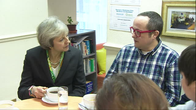 Interior shots of Prime Minister Theresa May sitting around a table talking to MCCH volunteers and staff at The Wellbeing Centre Hart Rushmoor in...